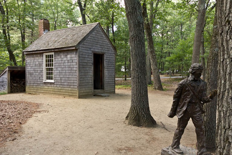 Henry David Thoreau'nun Walden Gölü yakınlarında yaşadığı kabinin replikası ve önündeki heykeli